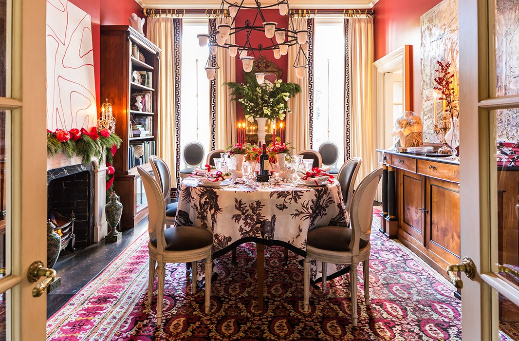"""I'm lucky to have a red dining room, so half the work is done,"" laughs Alessandra of the heart of her home come Christmastime, where her Jansen dining chairs, antique Agra rug, and 1950s French chandelier are joined by lush, leafy greenery."
