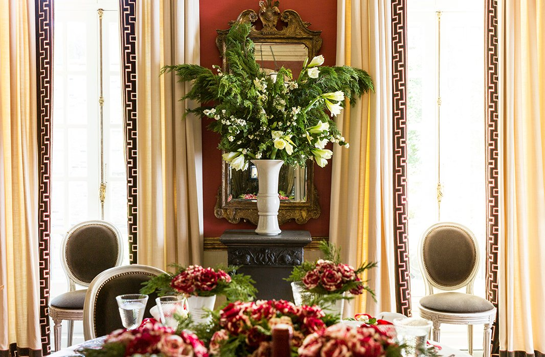 Leafy greenery overflow on the table, while a blooming vase of pine branches, winter greens, amaryllises, and white berries stands in for a tree and steals the spotlight as a floral centerpiece.