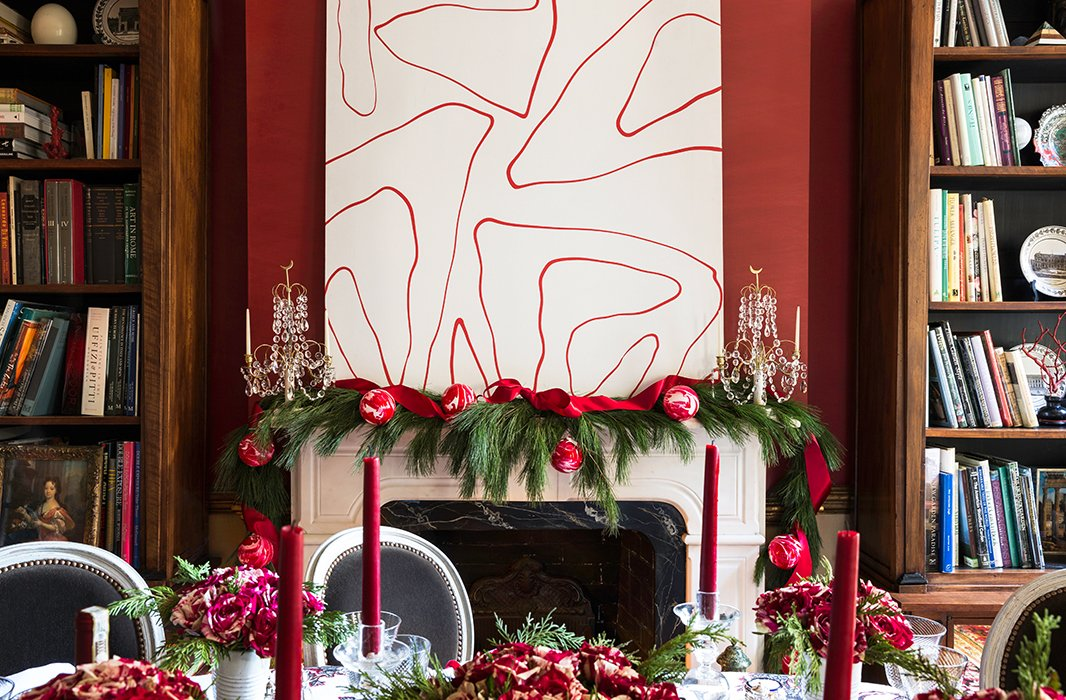 "A 1970s abstract painting offsets the Victorian mantel, which Alessandra dresses up with a simple full garland. For ""just a tiny bit of bling,"" 18th-century Swedish candelabras do the trick, while red tapers bring the soft glimmer she loves. ""My dining room at night is all candlelit."""