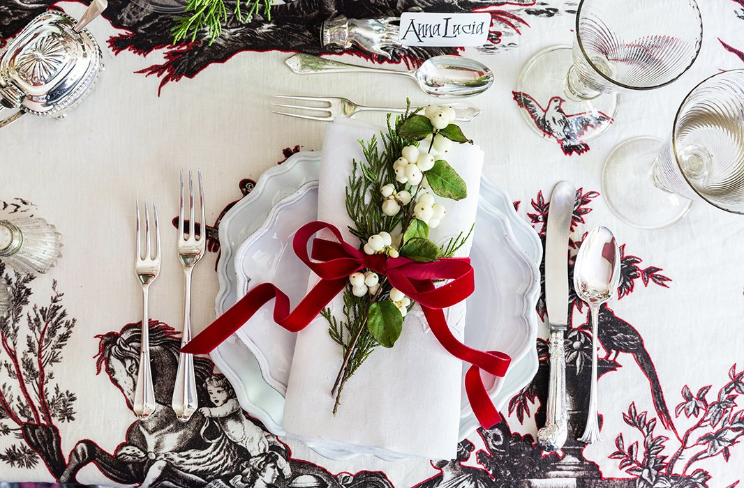 The place settings feature dishes by Astier de Villatte, embroidered napkins, and 18th- and 19th-century silver; a velvet bow and a sprig of pine and white berries is in keeping with Alessandra's festive palette.