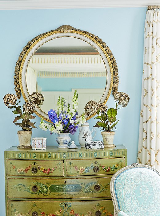"Bunny bought this painted English chest at an auction; the mirror is a carved French antique, and the ""hydrangeas"" and their pots are all made of tole."