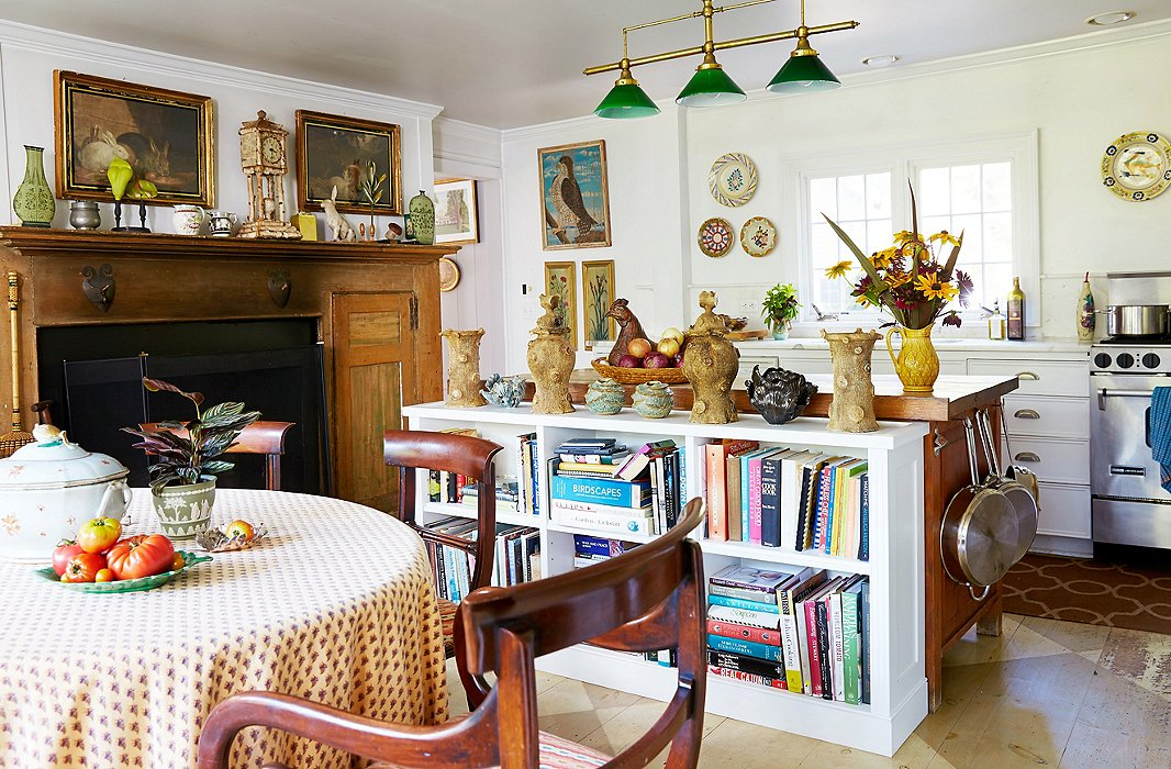 "The kitchen features modern appliances alongside the house's original 18th-century fireplace; the ""tree trunk"" pottery pieces atop the bookcase are antique."