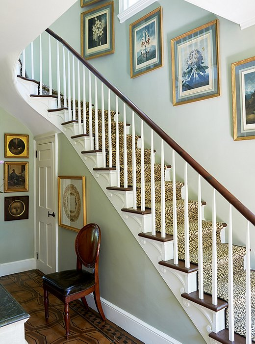A leopard-print runner makes a playful contrast to a set of 18th-century botanical prints hanging above the staircase.