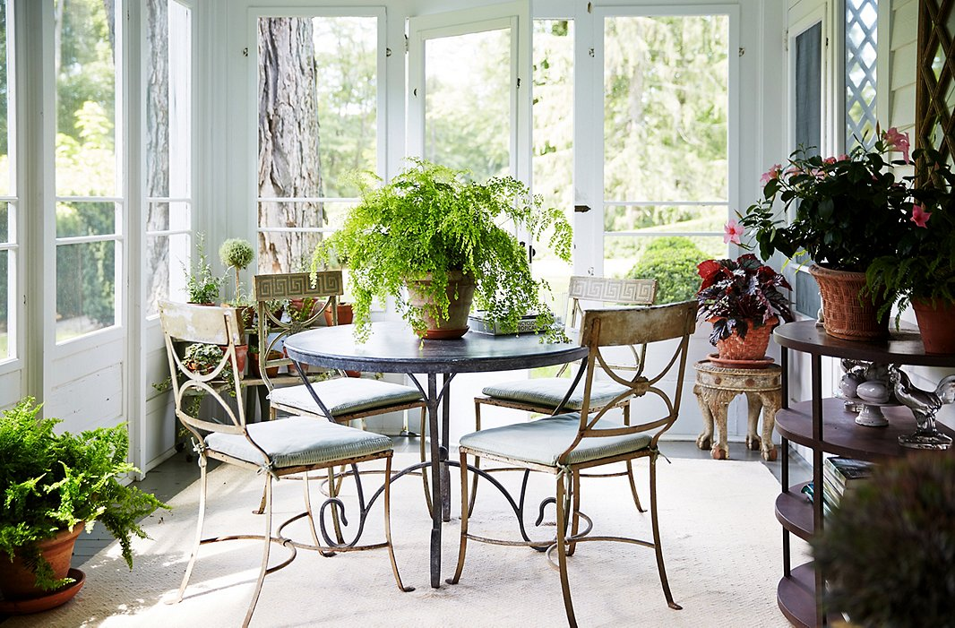 "A slightly worn table and set of chairs are perfectly at home on the porch. ""I don't want to go in a room where everything needs restoring,"" says Bunny. ""But there is something about patina that is relaxing."" The washable rugs are from her collection for Dash & Albert."
