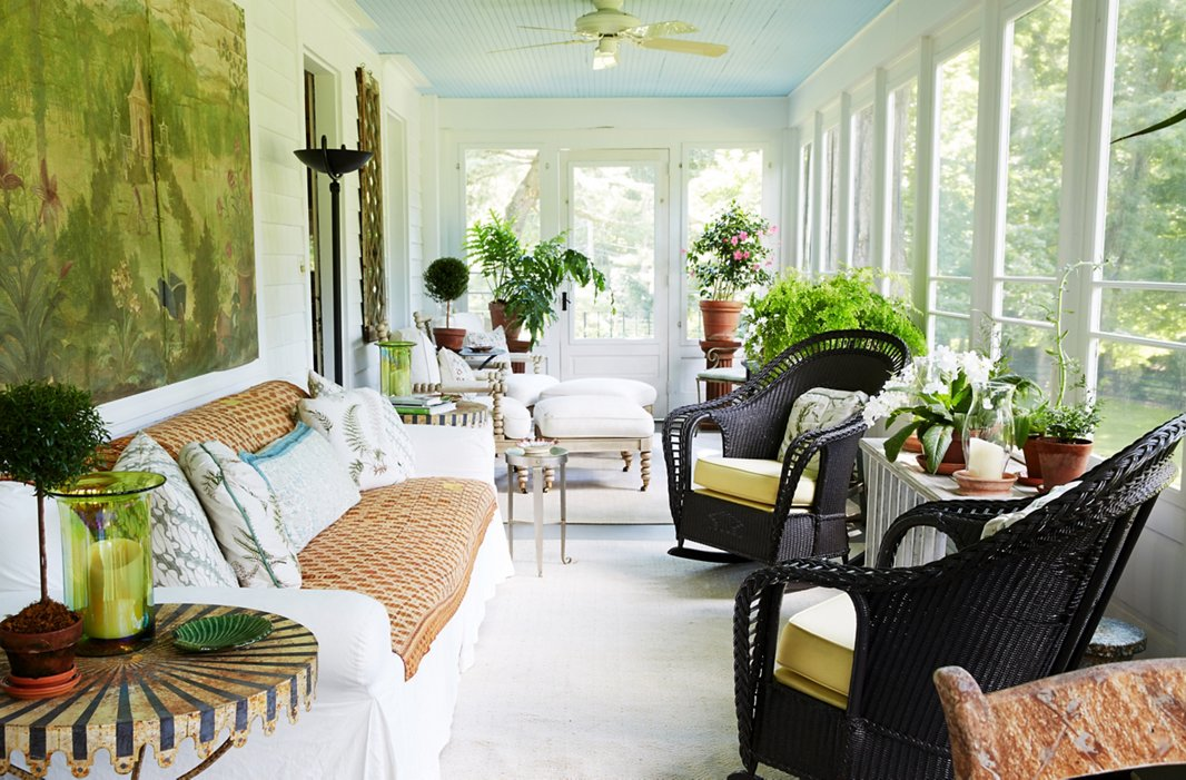 "The porch—which features screen windows in the summer and glass ones in the winter—runs the length of the house. Bunny used a natural-tone palette so that ""when you are in this room you feel like you are already in the garden."""