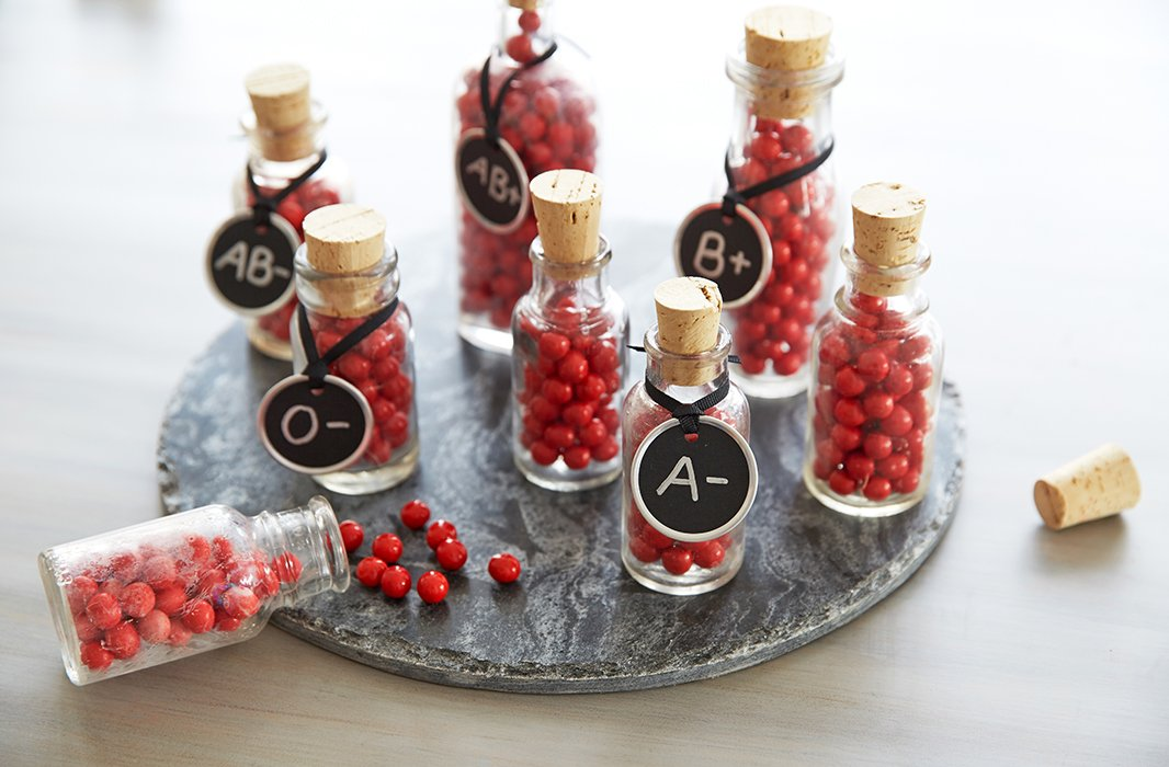 Mini corked apothecary bottles filled with tiny red candy balls mimic blood vials for simple and fun favors.