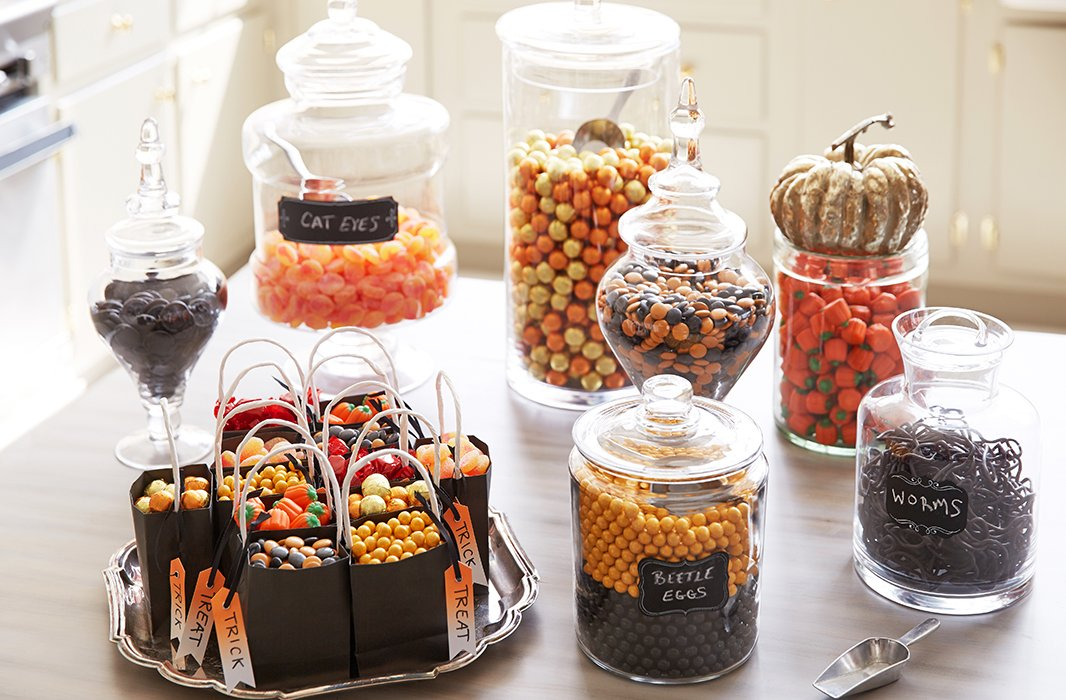 Glass canisters and apothecary jars in varying shapes hold gummies, chocolates, and other sweets in a captivating Halloween-inspired palette.