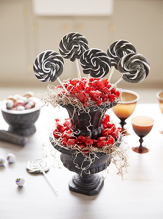 Stacked urns overflowing with sweets in red, white, and black make a showstopping lollipop display.