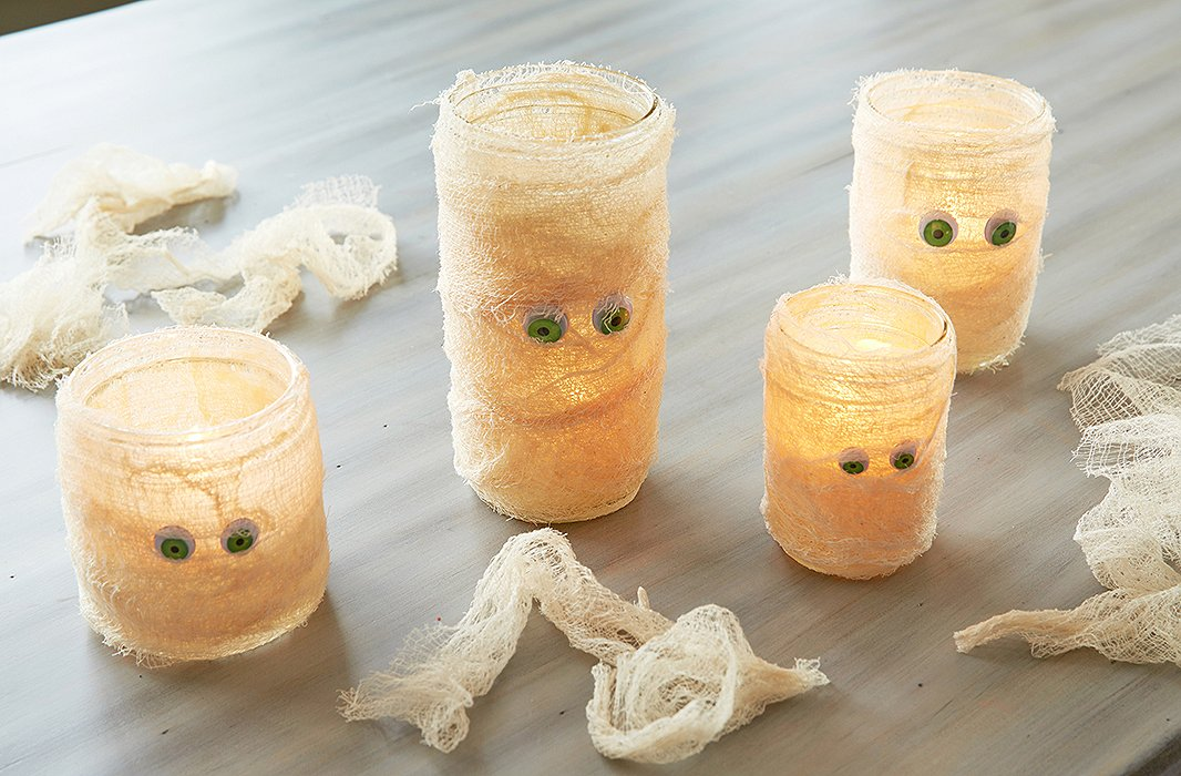 Cheesecloth-wrapped mason-jar candles make for dim mood lighting while serving double-duty as adorable mummies.