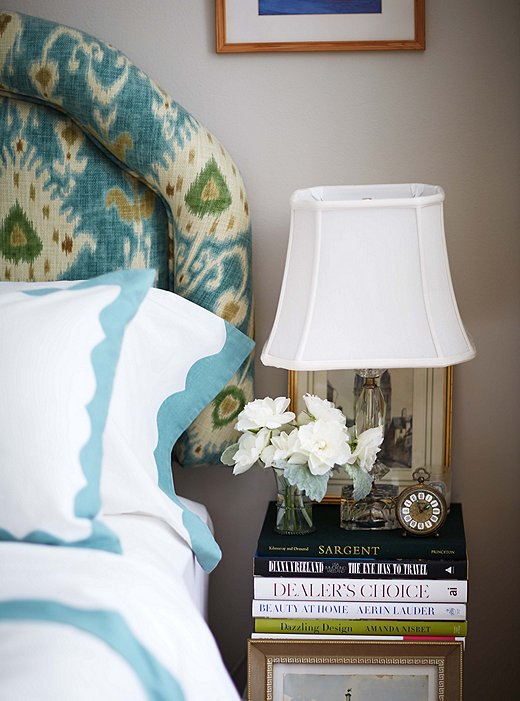 Fresh flowers add a note of polish to the bedside tables, which are made up of giant stacks of beautiful books.