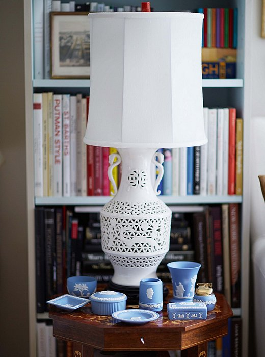 A collection of Wedgwood sits with a blanc de chine lamp.