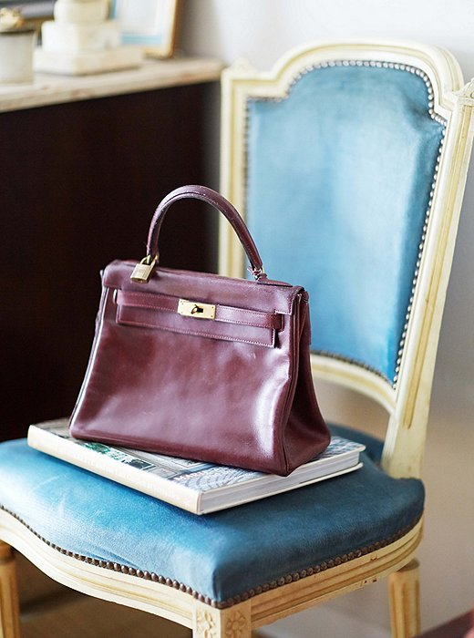 An Hermès bag perched on a French side chair. Upholstered in sky-blue velvet, the chair looks airy during the warm months and cozy in the winter.