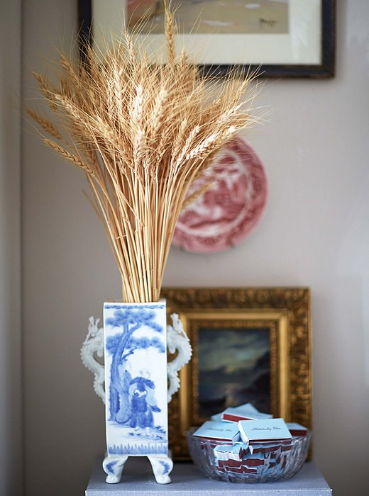 Wheat brings a natural note to a chinoiserie vase and balances the more ornate gilt frame and intricately painted plate.