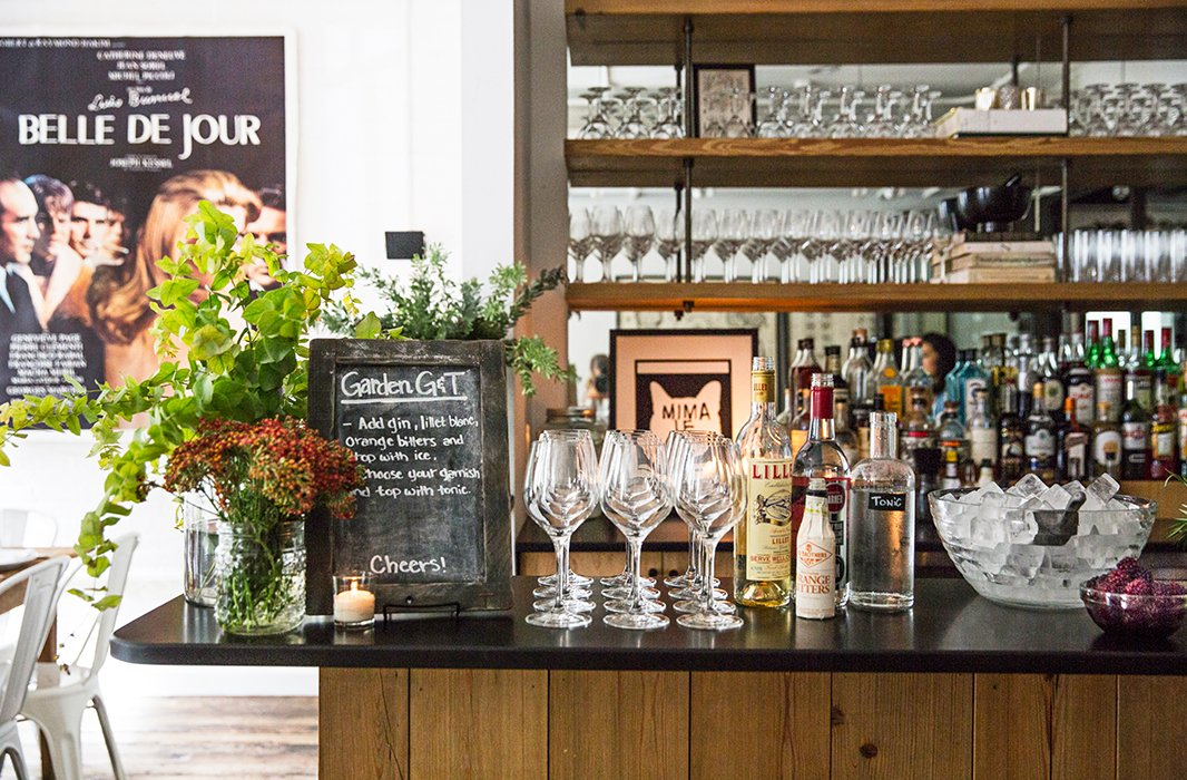 "A chalkboard sign tells guests the easy steps to making their own Garden Gin and Tonic: ""Add gin, Lillet Blanc, orange bitters, and top with ice. Choose your garnish and top with tonic."""