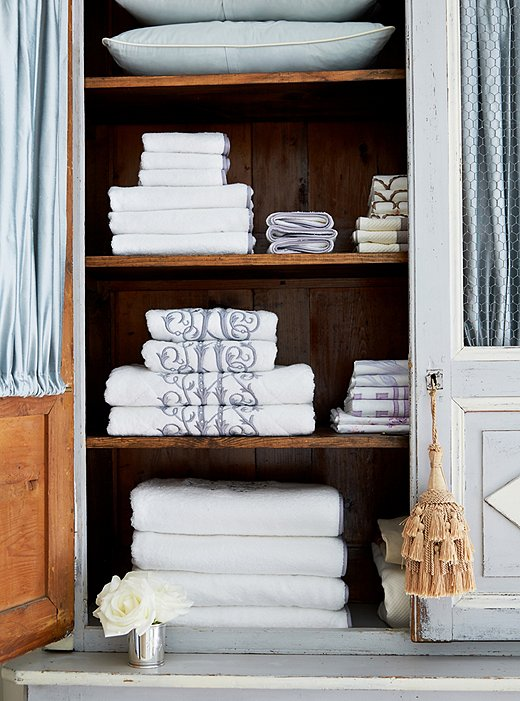 Fabric panels added inside the armoire-turned-linen closet conceal stacks of monogrammed towels by Leontine Linens.