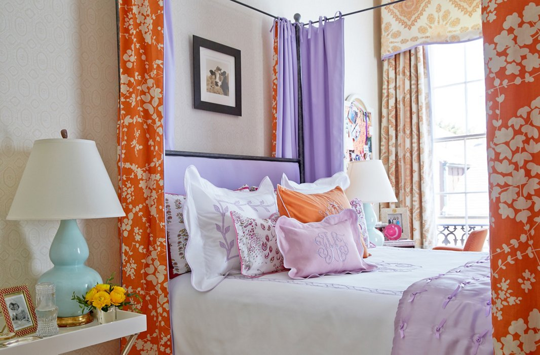 Linens and drapery in orange and lavender make for a dreamy guest bed.