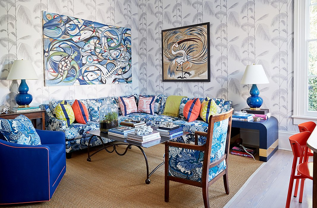 The den features artwork by her friend Alex Beard atop Cole & Son's Palm wallpaper.