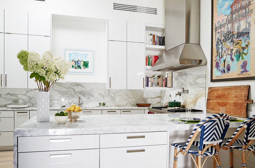 Framed artwork, striped bistro stools, and colorful cookbooks on open shelves add dimension to the all-white kitchen.