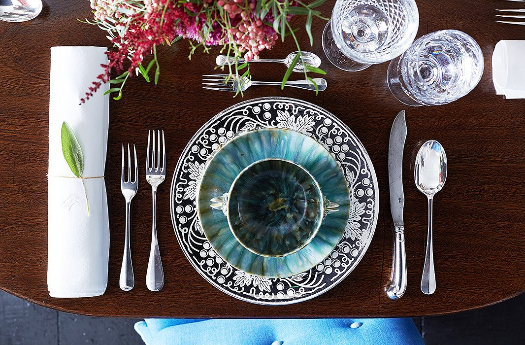 In lieu of a fanciful tablecloth, Jeffrey laysout American platinum-leaf lusterware chargers and English pottery plates and bowls for the idealtouch of pattern and texture.