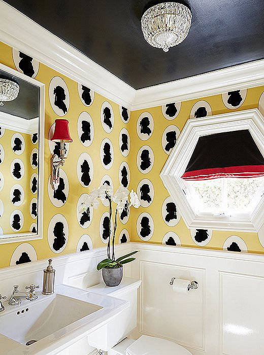 The yellow, black, and red palette and traditional fixtures give the playful silhouettes of the wallpaper a more refined edge.