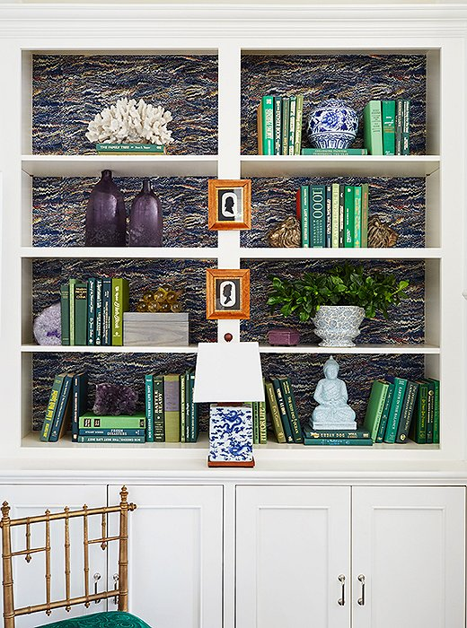 Painting or wallpapering the back of your shelves helps visually fill empty spaces and adds a flash of personality. Photo by Jessica Sample.