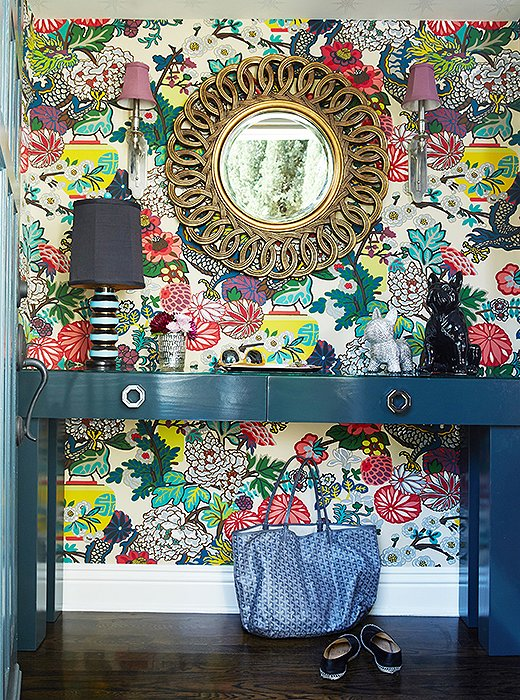 When it comes to embracing color,Jenn goes all-in.To balance suchan extravagant print, she chose a deep-tealentry table and a gold mirror.