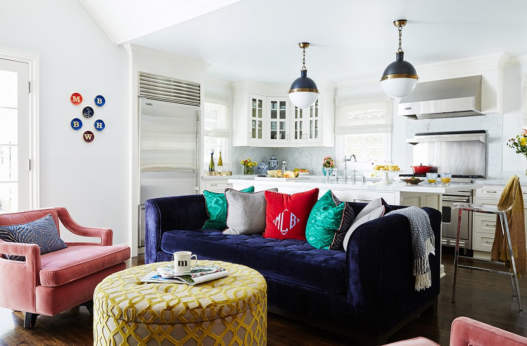 Feldman kept the macro palette white and the window treatments neutral, but her sense of playfulness is evident in the mix of pillows and personal family touches (note the monogrammed throw pillow and the initialed plates on the wall).