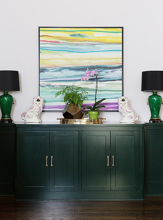 Black shades never fail to chic things up,and traditionaltouches like these lamps andStaffordshire dogfiguresbalance out the modern painting hung above.