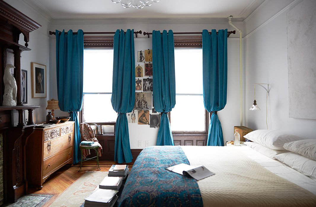 The unpainted wood and a dangling bedside lamp speak to the simple beauty of the house's original state. Jodie added billowing blue curtains for some grandeur.