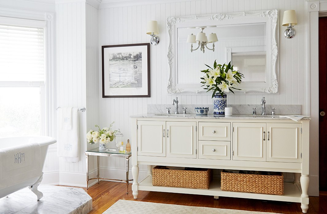 Awash in carrara marble the beadboard walled master bath is a breezy departure from