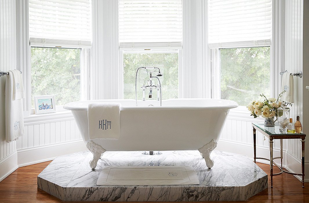 """I wainscoted the walls, had the whole room painted with Ralph Lauren's Brilliant White, and designed a Carrara marble platform so the new claw-foot Cheviot tub would have a perfect-height view of the pool gardens,"" says Delaney of her master bath revamp."