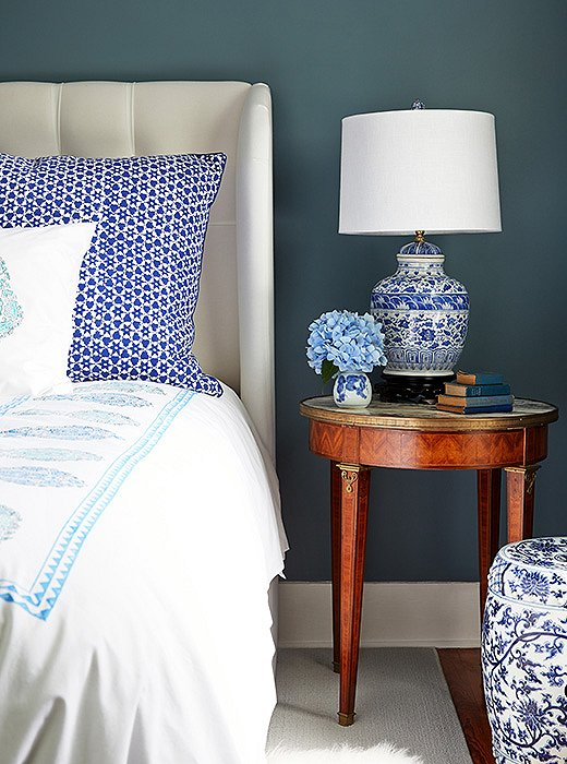 """I love a blue-and-white color palette and mixing and matching patterns and textures,"" says Delaney. Nowhere is that more evident than by her bedside, where a chinoiserie garden stool and lamp live in harmony with a mix of brightly printed Indian bedding."