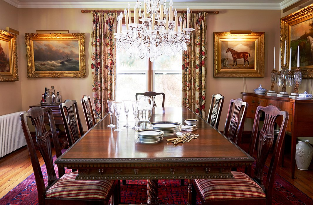 The sunlit dining room is decorated in warm tones and textures, from the Edwardian dining table to the Persian rug to the dining chairs upholstered in a Ralph Lauren tartan. A 19th-century Czech crystal chandelier presides over the scene.