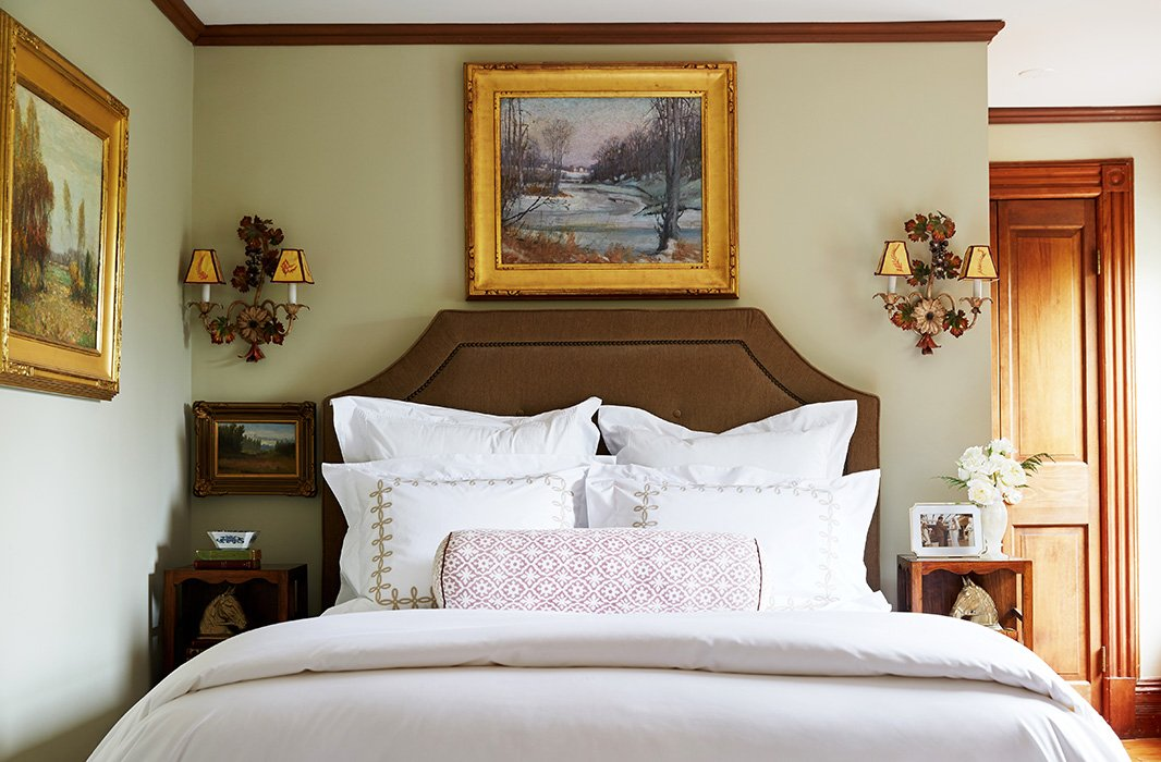In a guest bedroom, Delaney again favors symmetry, flanking a custom-upholstered linen headboard with a pair of Italianate sconces. Sumptuous bedding by Matouk and Yves Delorme makes for an inviting place of rest.