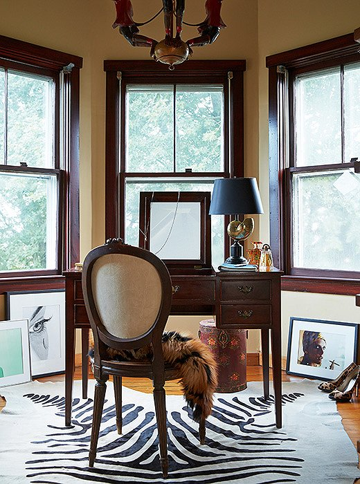 Nestled into the home's traditional Victorian turret is Delaney's home office. When she moved to the Hamptons, she brought along several pieces from her prewar apartment in Manhattan, including the antique monkey chandelier from William-Wayne & Co. Antiques that hangs above her desk.