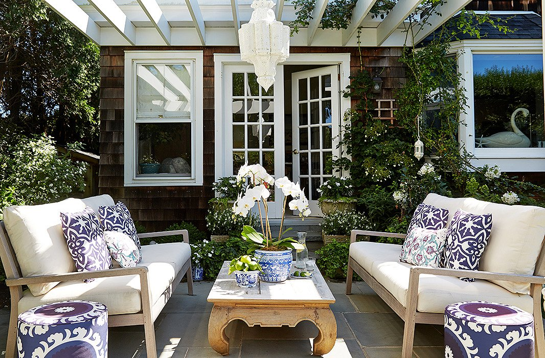 "In summer Delaney and Kot spend as much time outdoors as they do inside the house. When she moved in, Delaney added an ""entertaining space"" off the kitchen with a large bluestone patio and cedar pergola, which she decorated with Eastern-inspired flair, adding Moroccan-style hanging lanterns and suzani-print poufs."