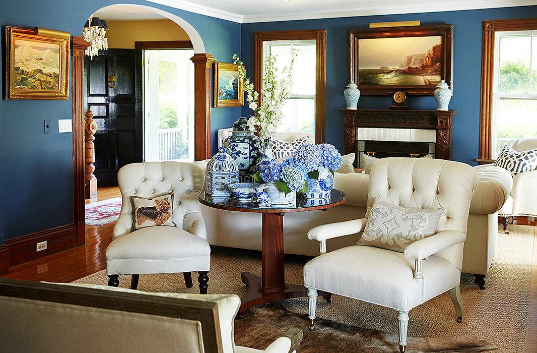 In the living room, a sampling of Delaney's collection of antique chinoiserie pieces cluster artfully on an 18th-century English tilt-top table surrounded by tufted French linen chairs from English Country Antiques in Bridgehampton.