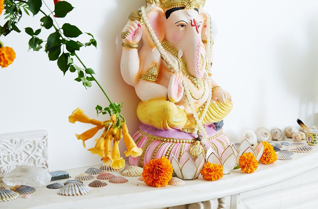 A Ganesha—a beloved Hindu deity believed to remove obstacles—sits over orange marigolds and scallop shells on Kelly's mantelpiece.