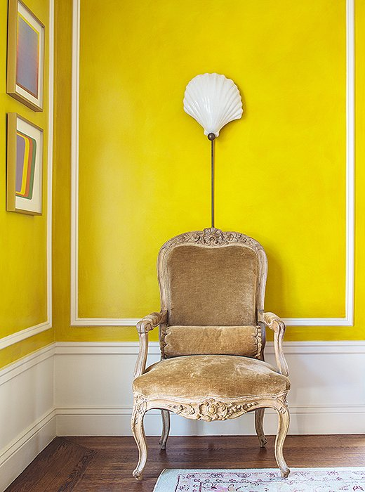 The chair, a French fauteuil in Louis XV style that Bachmann bought in London, is paired with a shell sconce from Past Perfect, a local vintage boutique.