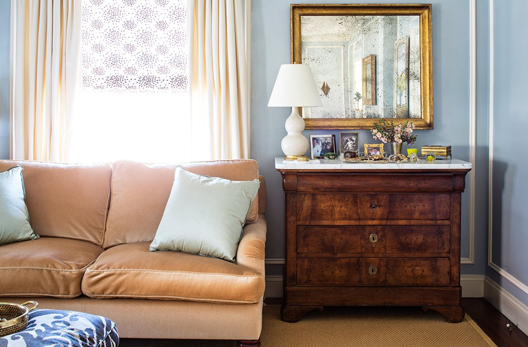 Subtle splashes of pattern—in the form of the lilac window shade and the blue footstool—enliven a purposefully pale palette.