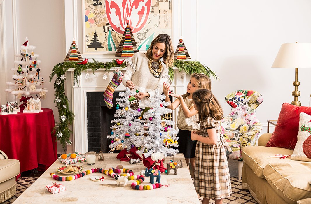 On a table next to the mantel, the girls' finished mini trees are used to create a charming holiday scene, complete with festive ceramic houses.