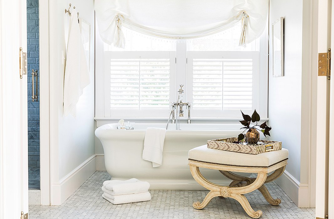 An antique bench brings a second neutral shade—a soft cream—to the bathtub zone.