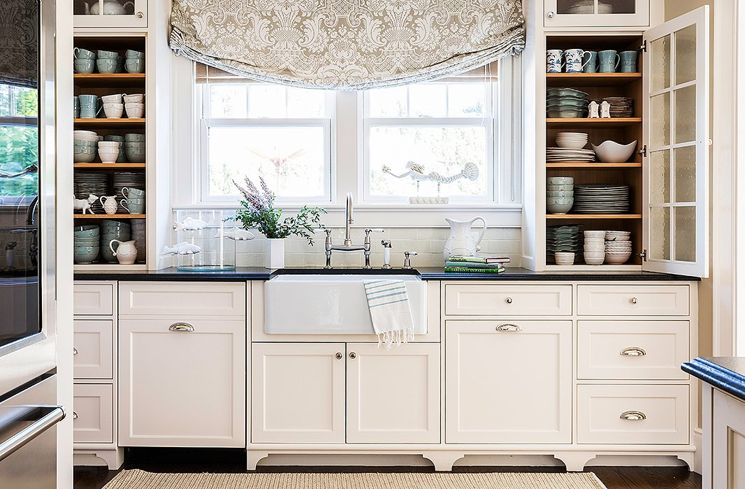 Against the cream color, the kitchen's textures really pop: the glossy countertops, the soft linen drapery, the fibrous rug.