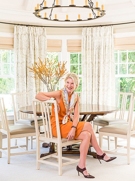 Mollie, basking in the beige of the dining room—and adding her own shot of orange.