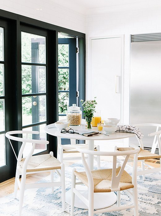 The breakfast table sits on one end of the kitchen, where French doors open out to an English garden.