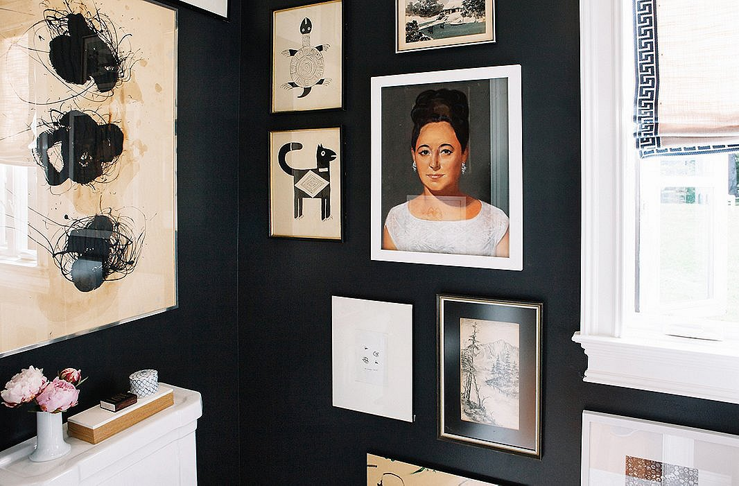 The ground-floor bathroom is painted black, to echo the all-black upper floor. A dramatic Cuban portrait stands out on the otherwise black-and-white gallery wall.