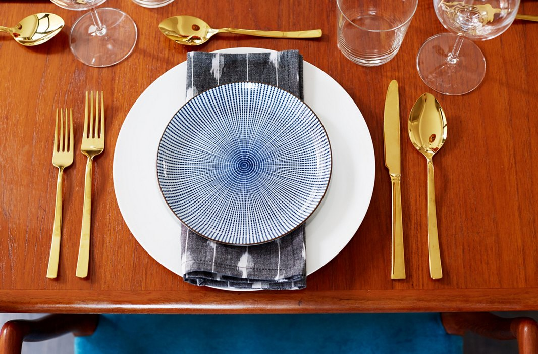 The table setting ready for action: glamorous gold instead of silver, and a plate that channels that classic blue-and-white combination in an unexpected way.