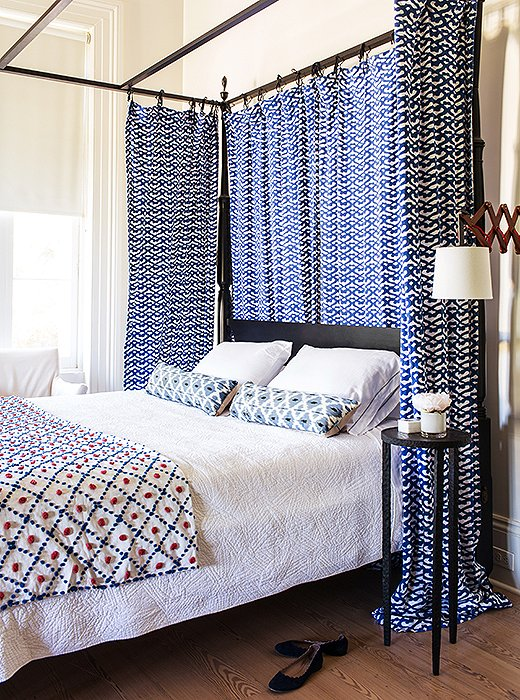 While eldest son Harrison was off at boarding school, Sara turned his room into a guest room. Roller Rabbit fabric that had previously served as kitchen curtains in New York now hang from the canopy. The colorful throw was found in a thrift store.