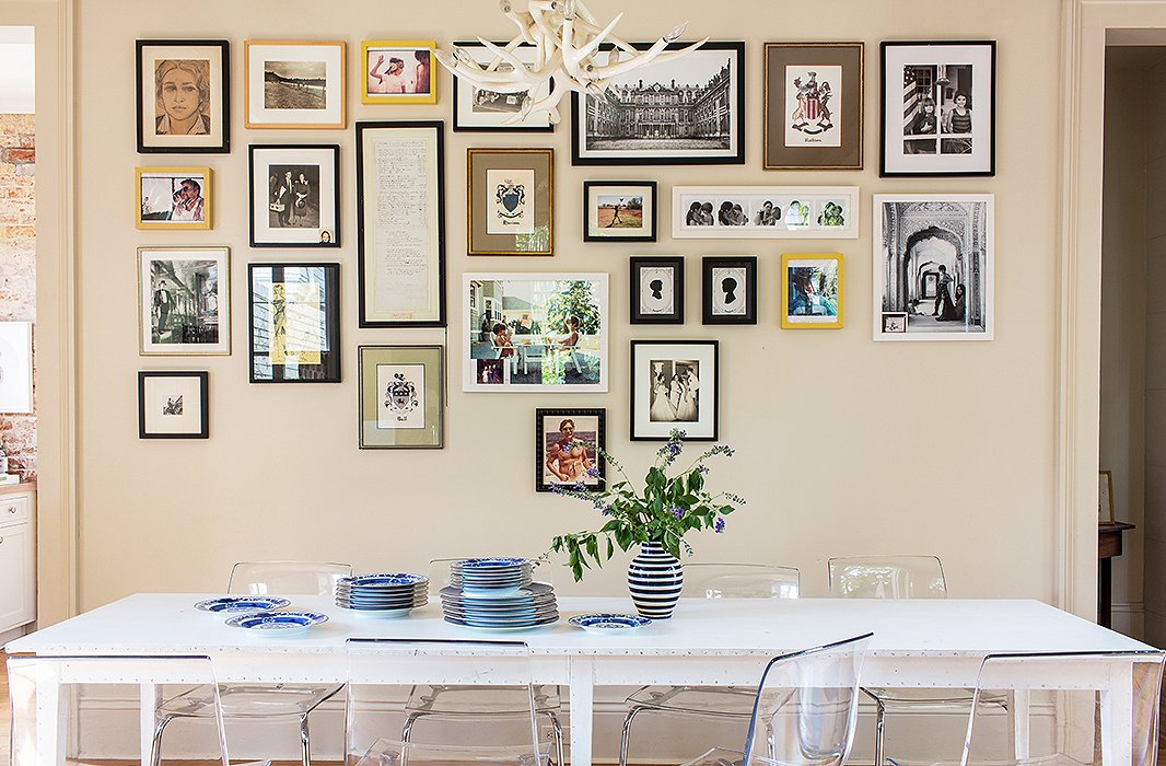 "A neat grid of family photos (still in progress) hangs over the kitchen table, a ""vintage '90s"" piece by fashion designer Ann Demeulemeester where the family eats all its meals. The plates are by Mottahedeh."