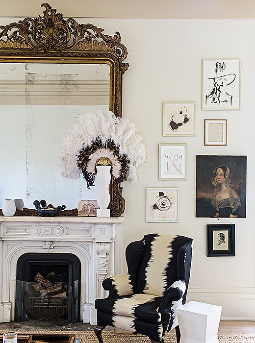 Sara kept the massive ornate mirror that came with the house and hung artwork—including spin art by designer Miles Redd and an old family portrait—floor to ceiling to help fill the incredibly high walls.